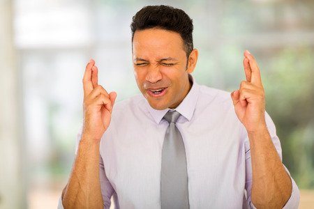 finger crossed: corporate worker with finger crossed in modern office