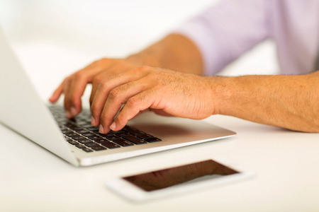 close up of man hands working on laptop photo