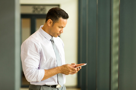 tie: handsome middle aged businessman texting on his smart phone