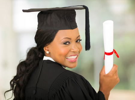 happy african college graduate looking back over her shoulder photo