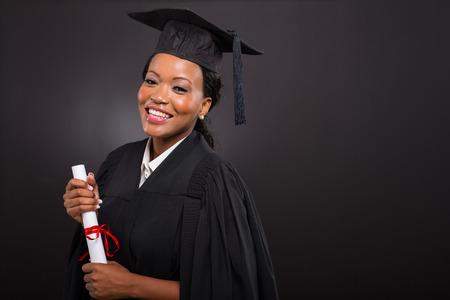 studio portrait of african college graduate on black background photo