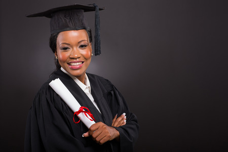 portrait of beautiful young african american graduate holding diploma photo