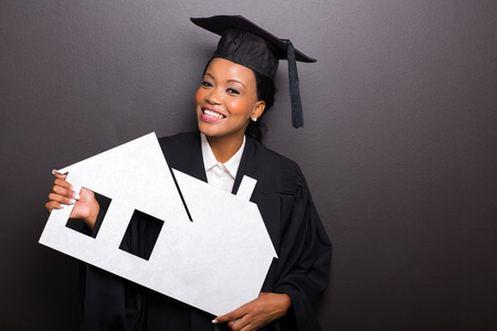 attractive african female university graduate holding white paper house photo