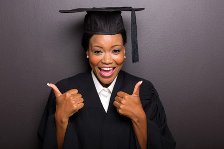 college: cheerful afro american female college graduate thumbs up