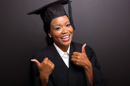 close up portrait of african female university graduate thumbs up photo