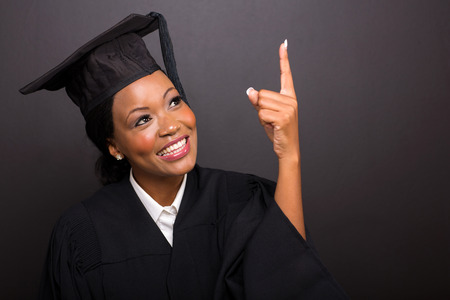 cheerful young african american graduate pointing up on black background photo