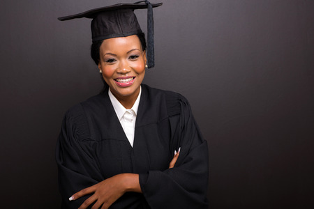 beautiful female college graduate with arms crossed on black background photo