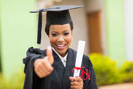 beautiful african female graduate giving thumb up at graduation ceremony photo