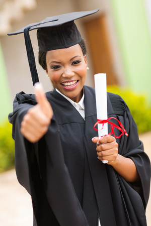 african american female graduate thumb up outside college building photo
