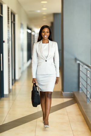 beautiful young african career woman with briefcase walking in office building
