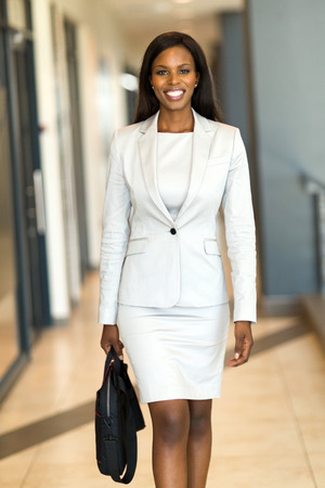 modern businesswoman: cheerful african american business executive with briefcase in office building Stock Photo