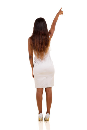 rear view of young african woman pointing at empty copy space photo