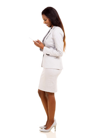 白で隔離の携帯電話を使用してかなりアフリカのビジネス女性の側面図