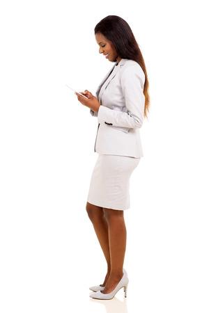 zijaanzicht van mooie Afrikaanse vrouw met behulp van mobiele telefoon geïsoleerd op wit Stockfoto