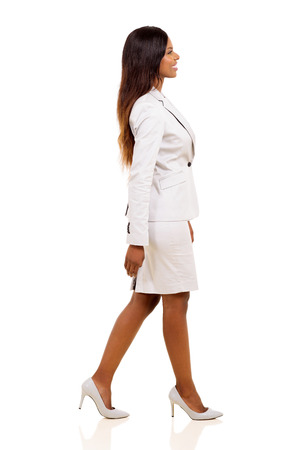 african american woman smiling: side view of young african american businesswoman walking on white background