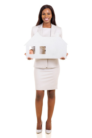 happy african business woman holding house symbol on white background photo