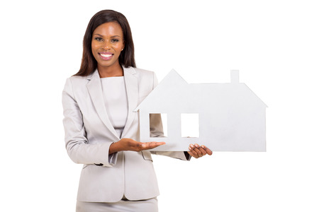 cheerful african businesswoman showing house symbol on white background photo