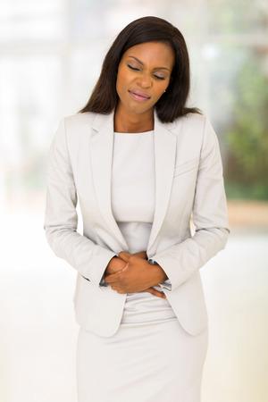 dolor de estomago: Mujer africana joven que tiene dolor de estómago en el cargo