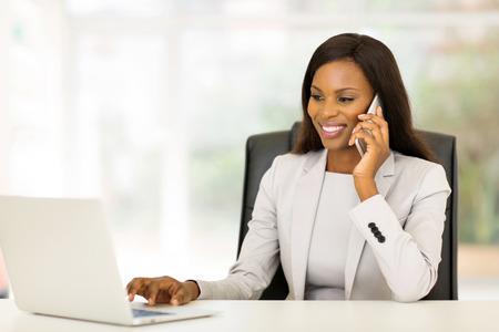 profesionistas: empresaria bonita del afroamericano que usa el tel�fono m�vil Foto de archivo