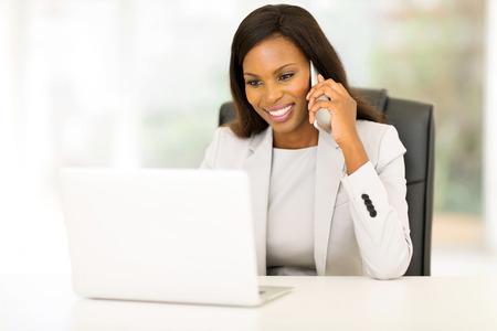 felice di affari africana americano parlando al cellulare in ufficio