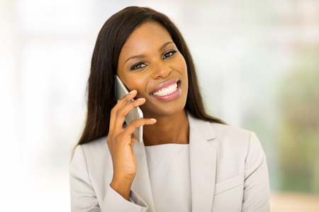 confident woman: cheerful young afro american woman talking on cell phone