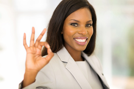 african american businesswoman: cheerful african american businesswoman giving ok hand sign Stock Photo