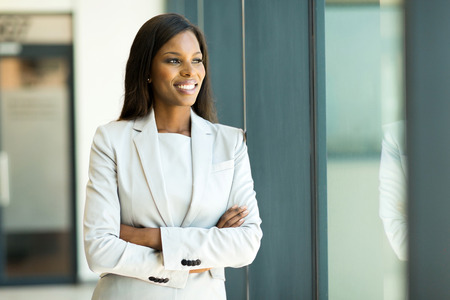 charming business lady: happy young african businesswoman looking out the window Stock Photo