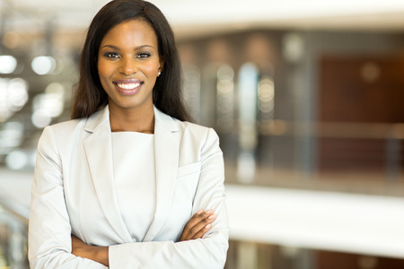 african american woman smiling: attractive black business executive with arms crossed