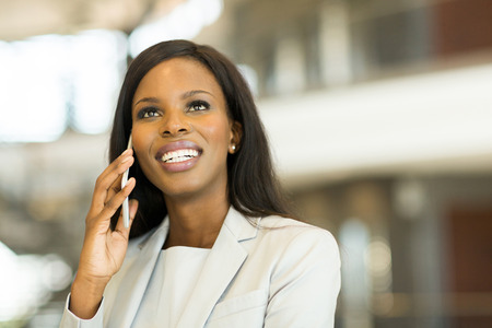 business woman phone: young businesswoman talking on cell phone in modern office Stock Photo