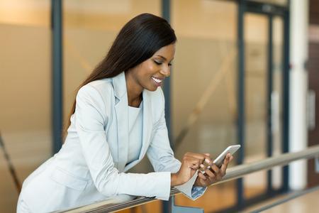 professionelle junge afrikanische Karrierefrau mit Smartphone Standard-Bild