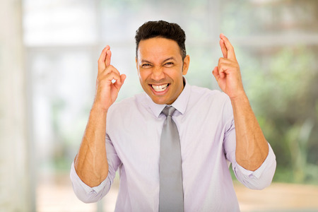 finger crossed: good looking middle aged business executive with finger crossed