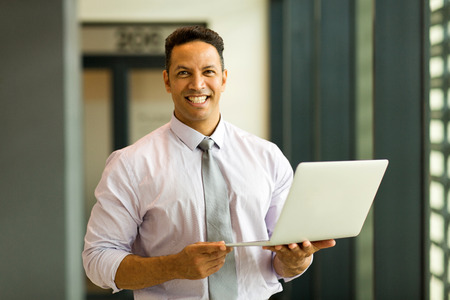 mid age: portrait of mid age employee holding laptop