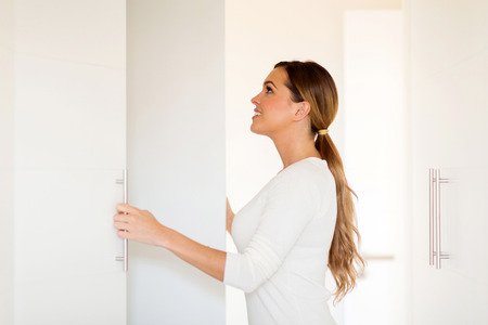 woman closet: beautiful young woman opening wardrobe doors Stock Photo