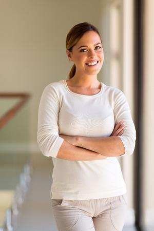 mujeres: hermosa mujer joven con los brazos cruzados en el hogar