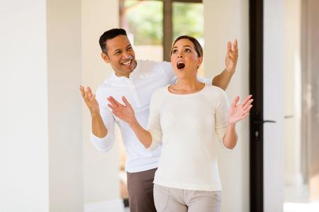 sorpresa: feliz hombre de mediana edad asombrosamente su esposa con una nueva casa Foto de archivo