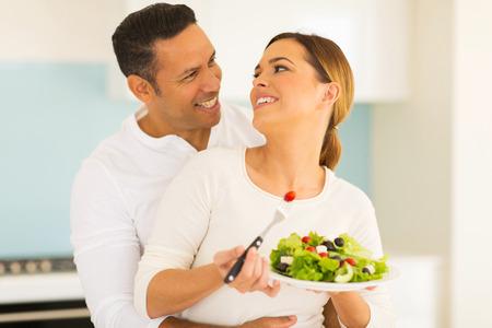 pareja comiendo: hermosa pareja comiendo ensalada en casa Foto de archivo