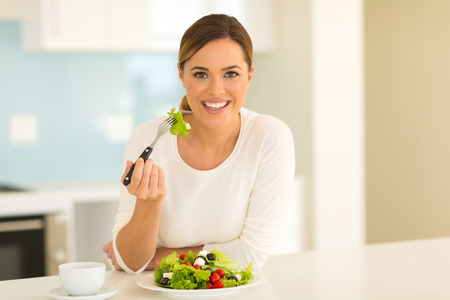 eating utensils: healthy young woman eating green salad at home