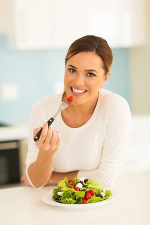 beautiful young woman eating green salad