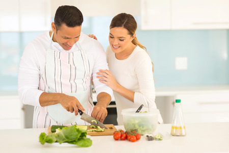 kitchen aprons: beautiful couple cooking together in home kitchen