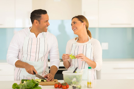 food woman: cheerful couple cooking together at home