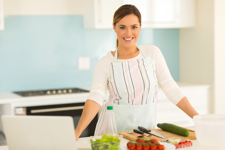 happy woman in a modern kitchen making salad photo