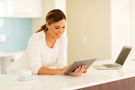 donne eleganti: pretty young woman using tablet computer at home