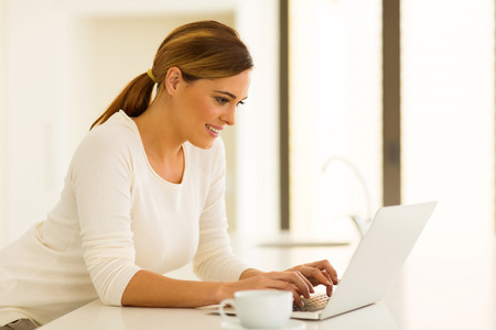 looking at computer screen: beautiful young woman using laptop at home