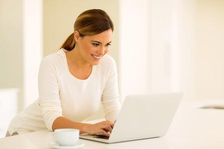 correo electronico: feliz joven mujer de mensajes de correo electrónico de lectura en el ordenador portátil en la cocina