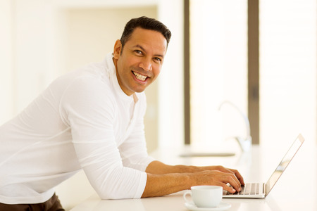 good looking: good looking mid age man with laptop in kitchen Stock Photo