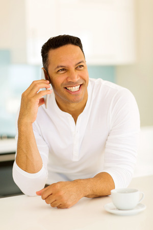 mid age: happy mid age man talking on cell phone at home Stock Photo