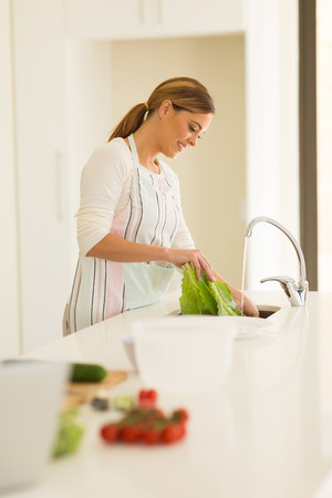 beautiful housewife washing vegetables in the kitchen photo