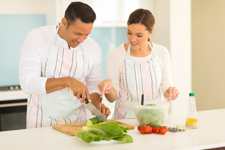 beautiful middle aged woman: woman teaching husband cutting vegetables in kitchen