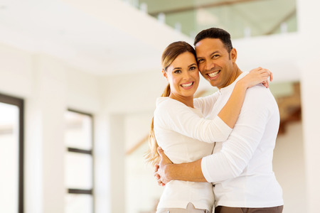matrimonio feliz: feliz pareja abrazándose en su nueva casa Foto de archivo
