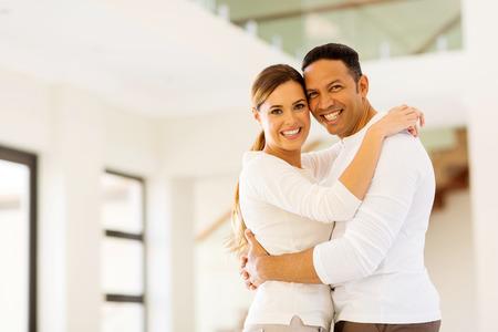 matrimonio feliz: feliz pareja abraz�ndose en su nueva casa Foto de archivo